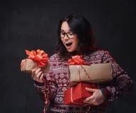 Una mujer en lentes sostiene los regalos de la Navidad foto de archivo