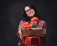 Una mujer en lentes sostiene los regalos de la Navidad fotografía de archivo