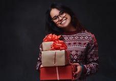 Una mujer en lentes sostiene los regalos de la Navidad foto de archivo libre de regalías