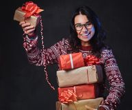 Una mujer en lentes sostiene los regalos de la Navidad imagen de archivo