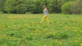 Una mujer en pantalones amarillos que camina a lo largo del campo del diente de león almacen de metraje de vídeo