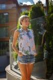 Una mujer en pantalones cortos del dril de algodón y camisa colorida Imagenes de archivo