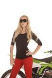 Una mujer en pantalones y vidrios de sol rojos delante de la motocicleta Imágenes de archivo libres de regalías
