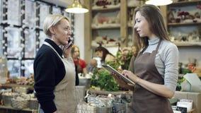 Una mujer en respuestas de un delantal la llamada de teléfono, y la muchacha en un delantal escribe sus instrucciones en una tabl almacen de video