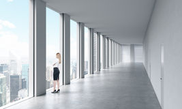 Una mujer en ropa formal está mirando hacia fuera la ventana Interior limpio brillante moderno vacío de una oficina del espacio a fotos de archivo