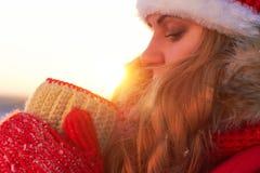 Una mujer, en ropa roja caliente, bebe té o el café caliente en la naturaleza en la puesta del sol caliente Imagen de archivo libre de regalías