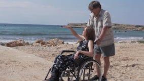 Una mujer en una silla de ruedas camina con su marido por el mar almacen de video
