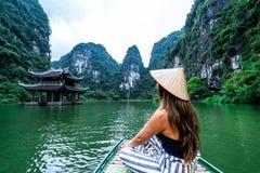 Una mujer en un barco de río en Ninh Binh Montañas de Vietnam septentrional foto de archivo libre de regalías