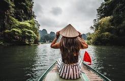 Una mujer en un barco de río en Ninh Binh Montañas de Vietnam septentrional foto de archivo