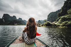 Una mujer en un barco de río en Ninh Binh Montañas de Vietnam septentrional imagen de archivo