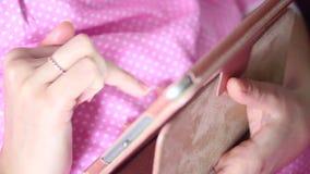 Una mujer en un camisón trabaja con una tableta mientras que miente en cama Ella toca la pantalla con sus fingeres almacen de video