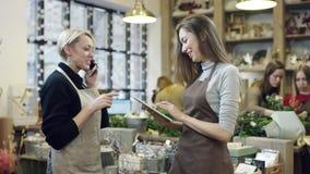 Una mujer en un delantal que habla en el teléfono y da las instrucciones a la muchacha en un delantal, muchacha observa sus instr almacen de video
