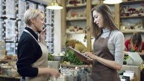 Una mujer en un delantal que habla en el teléfono, y la muchacha en un delantal escribe sus instrucciones en una tableta almacen de metraje de vídeo