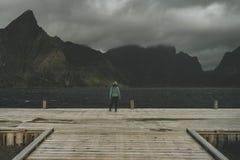 Una mujer en un embarcadero que hace frente al mar y a las montañas delante de ella foto de archivo