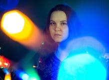 Una mujer en un fondo oscuro y luces fotos de archivo libres de regalías