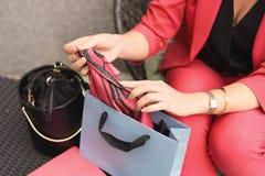Una mujer en un pantsuit que el color del coral vivo se sienta en una silla y que saca una bufanda fotografía de archivo