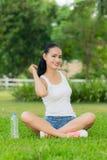 Una mujer en un parque con la botella de agua Imagen de archivo libre de regalías