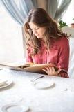 Una mujer en un restaurante con el menú en manos Foto de archivo
