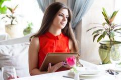 Una mujer en un restaurante con el menú en manos Foto de archivo libre de regalías