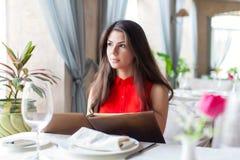 Una mujer en un restaurante con el menú en manos Imagen de archivo