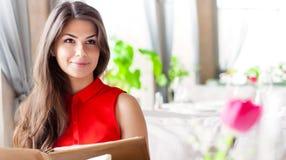 Una mujer en un restaurante con el menú en manos Imágenes de archivo libres de regalías