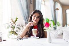 Una mujer en un restaurante está bebiendo el cóctel Foto de archivo