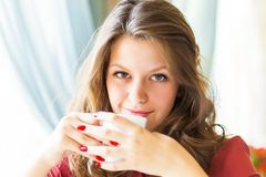 Una mujer en un restaurante está bebiendo el café Fotos de archivo libres de regalías