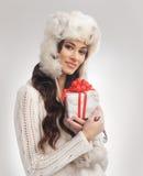 Una mujer en un sombrero caliente del invierno que lleva a cabo un presente Fotografía de archivo