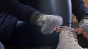 Una mujer en un suéter caliente y guantes engarza los patines blancos almacen de video