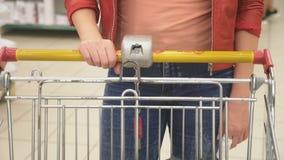 Una mujer en un supermercado está pasando por la cesta más allá de los contadores 4K metrajes