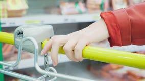 Una mujer en un supermercado está pasando por la cesta más allá de los contadores 4k, primer almacen de metraje de vídeo
