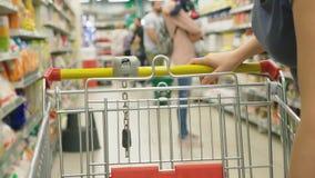 Una mujer en un supermercado está pasando por la cesta más allá de los contadores 4k, primer, una mujer camina alrededor del supe almacen de video
