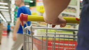 Una mujer en un supermercado está pasando por la cesta más allá de los contadores 4k, primer, una mujer camina alrededor del supe metrajes