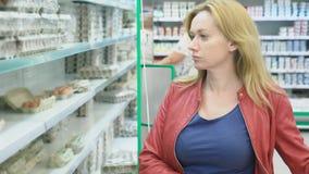 Una mujer en un supermercado está pasando por la cesta más allá de los contadores 4k, primer, una mujer camina alrededor del supe almacen de metraje de vídeo