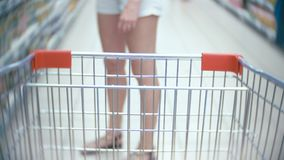Una mujer en un supermercado está pasando por la cesta más allá de los contadores 4k, primer, una mujer en los pantalones cortos  metrajes