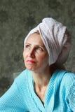 Una mujer en un traje azul con la toalla en la cabeza Fotos de archivo libres de regalías