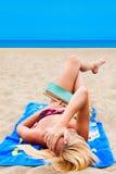 Una mujer en un traje de baño en una playa que lee un libro Foto de archivo libre de regalías