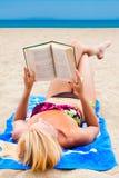 Una mujer en un traje de baño en una playa que lee un libro Imagen de archivo libre de regalías