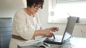 Una mujer en un traje de negocios y vidrios está trabajando con su ordenador portátil Hay cuentas de papel cerca Se inclina para  almacen de metraje de vídeo