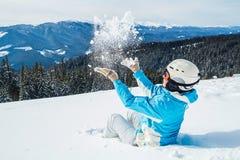 369c070476c Una mujer en un traje y una máscara azules de esquí lanza nieve en la cámara