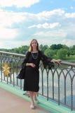 Una mujer en un vestido negro que se coloca en el puente Fotografía de archivo