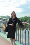 Una mujer en un vestido negro que se coloca en el puente Fotos de archivo