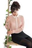 Una mujer se está sentando en un oscilación Imagen de archivo libre de regalías