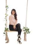 Una mujer se está sentando en un oscilación Fotos de archivo libres de regalías