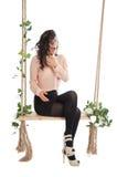 Una mujer se está sentando en un oscilación Imágenes de archivo libres de regalías