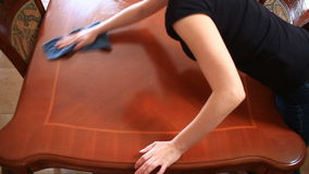 Una mujer en una camiseta negra apretada con un escote profundo limpia una tabla de cocina grande con un trapo almacen de video