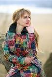 Una mujer en una capa coloreada con mucha tristeza y sufrimiento tensión Mujer triste al aire libre Imagen de archivo libre de regalías
