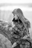 Una mujer en una capa coloreada con tristeza, y el sufrimiento con un dolor de cabeza en la playa Mujer triste al aire libre Fotografía de archivo libre de regalías