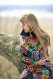 Una mujer en una capa coloreada con tristeza, y el sufrimiento con un dolor de cabeza en la playa Mujer triste al aire libre Imagenes de archivo