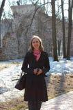 Una mujer en una capa negra que camina en el parque Foto de archivo libre de regalías